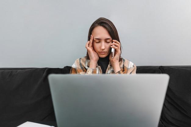 Moe vrouw met hoofdpijn praten op mobiele telefoon en werken op laptop