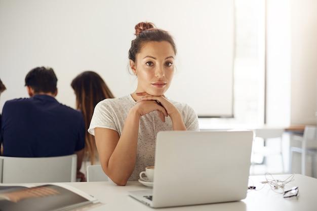 Moe vrouw met laptop na een werkdag in open kantoorruimte. jonge student op een universitaire campus die zich klaarmaakt voor examens.