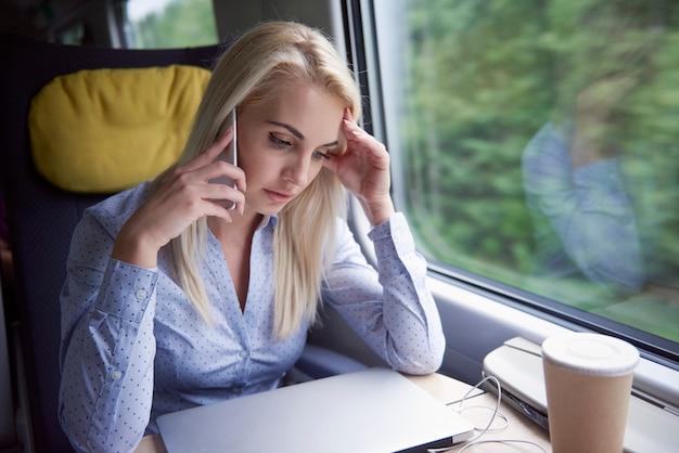 Moe vrouw praten via de mobiele telefoon tijdens de reis