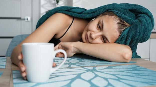 Moe vrouw slapen op de tafel. mooie vrouw in een handdoek op haar. hand reikt naar de mok