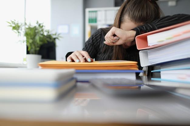 Moe vrouw slapen op papieren documenten in office