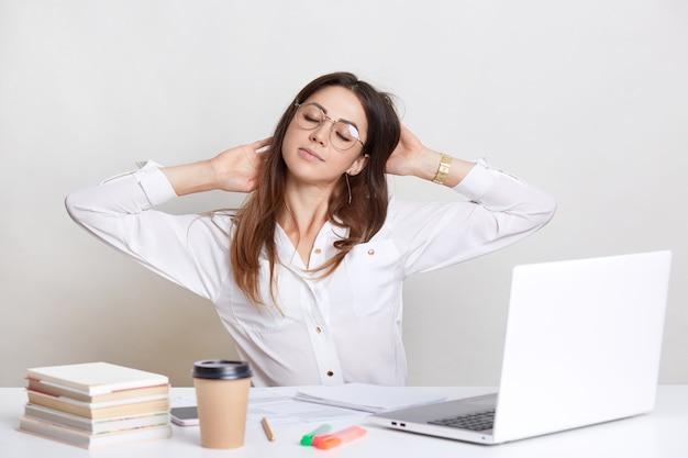 Moe vrouw strekt zich uit op de werkplek, draagt een wit overhemd en een bril, voelt zich aan het werk, zit voor een geopende laptop, drinkt afhaalkoffie om zich verfrist te voelen, geïsoleerd op wit