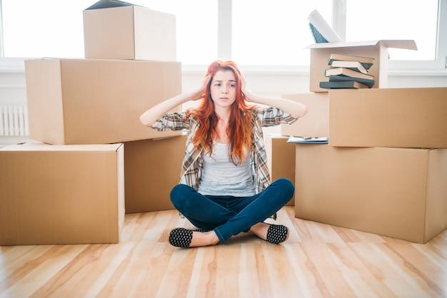Moe vrouw zitten in yoga pose onder kartonnen dozen, inwijdingsfeest. verhuizing naar nieuw huis