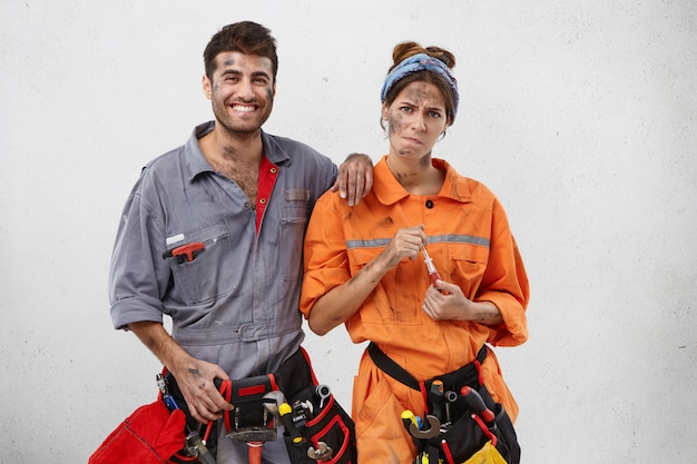 Moe vrouwelijke timmerman in oranje uniform, houdt schroevendraaier en mannelijke collega met gelukkige uitdrukking