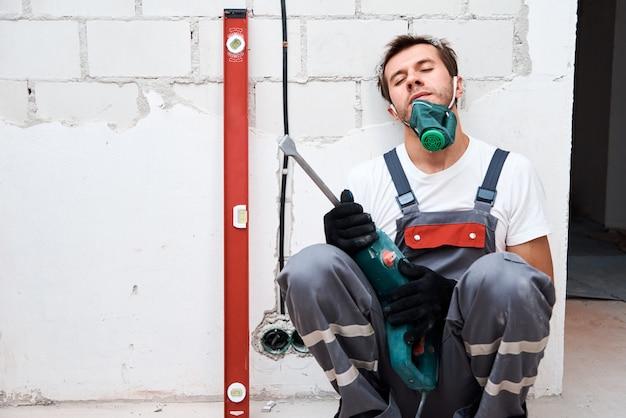 Moe werknemer man met een hamer boor op bouwplaats