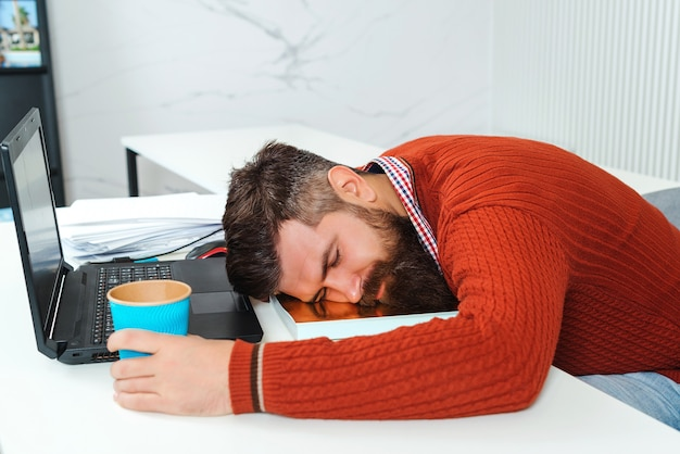 Moe zakenman slapen in kantoor. bebaarde man slapen op zijn werkplek.