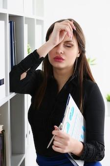 Moe zakenvrouw houden hoofd met arm