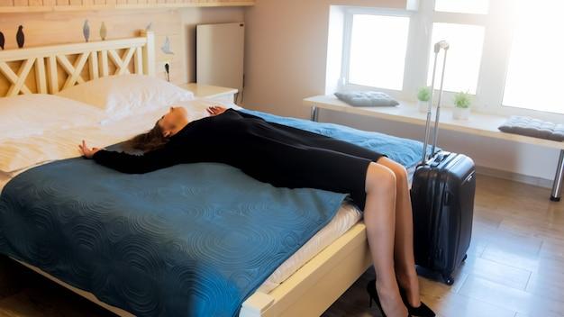 Moe zakenvrouw liggend op bed in hotelkamer na lange vlucht in vliegtuig