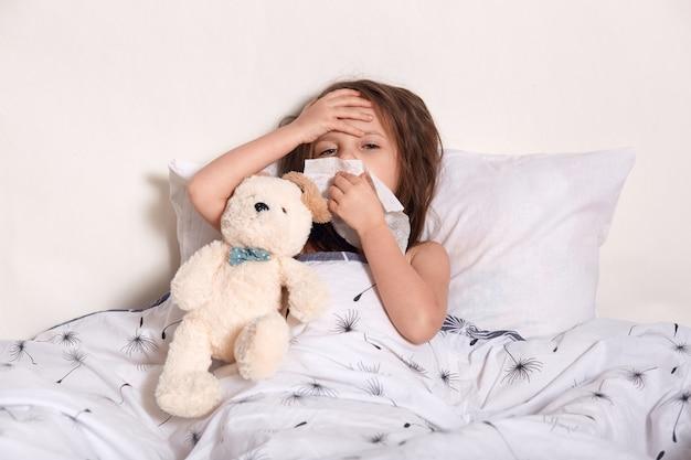 Moe ziek teleurgesteld klein kind met een hand op het voorhoofd