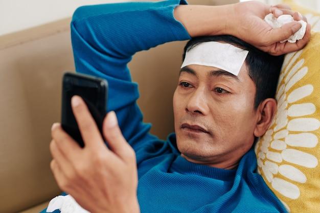 Moe zieke volwassen vietnamese man liggend op de bank met verkoelende patch op het voorhoofd en het lezen van nieuws over de behandeling van het coronavirus op smartphone