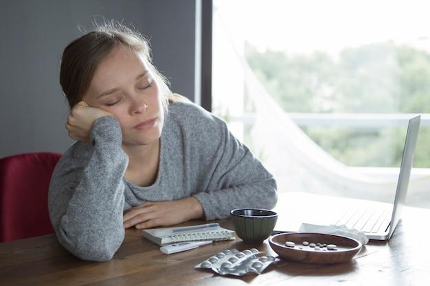 Moe zieke vrouw met gesloten ogen ontspannen na het werken op pc