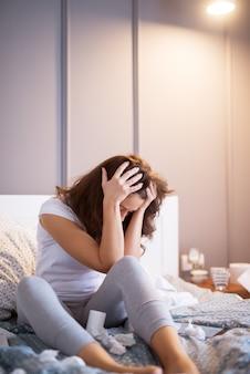 Moe zieke vrouw van middelbare leeftijd hand in hand op het hoofd terwijl papieren doekjes om haar heen op het bed.