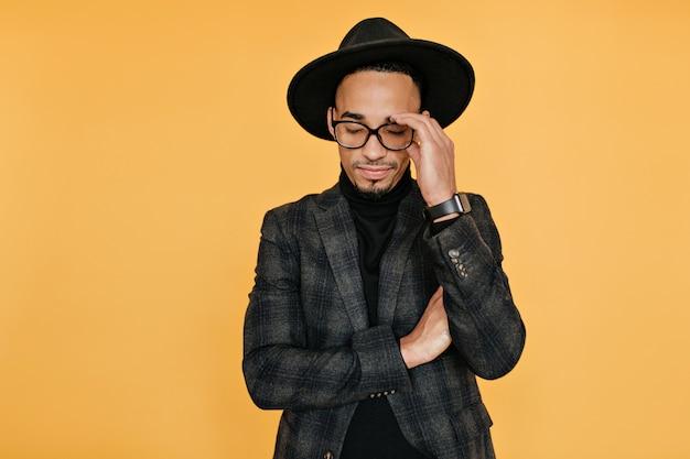 Moe zwarte jonge man in formele kleding poseren met gesloten ogen. foto van een afrikaanse man in trendy vrijetijdskleding staande op gele muur.