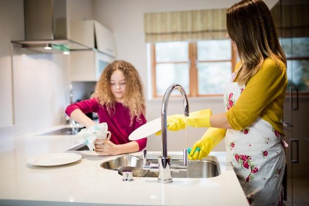 Moeder assisteren dochter in het wassen van plaat in keuken