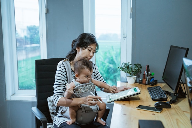 Moeder babysit haar baby baby tijdens het werken