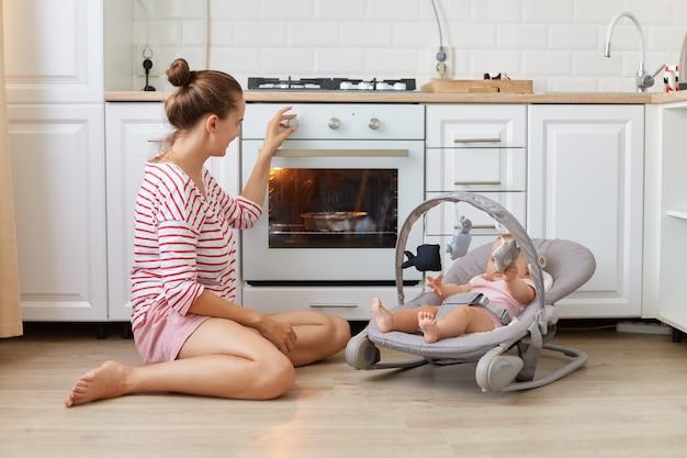 Moeder bakt een taart met haar pasgeboren dochter liggend in schommelstoel, jonge vrouw draagt casual stijl shirt en kind in uitsmijter koken in een witte keuken, gebak bakken, diner maken.