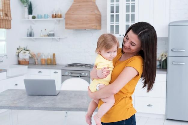 Moeder bedrijf baby in de keuken