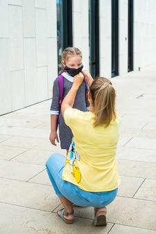 Moeder begeleidt haar dochter naar school