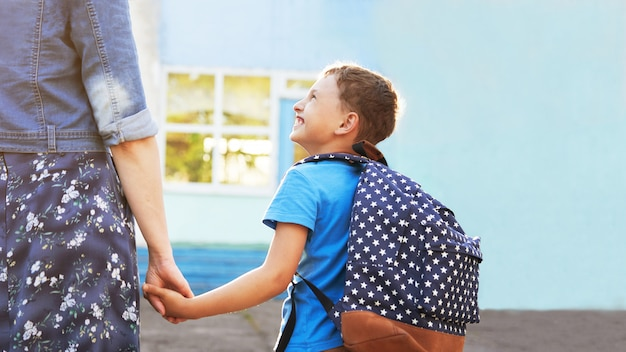 Moeder begeleidt het kind naar school. moeder moedigt studenten aan die hem naar school begeleiden