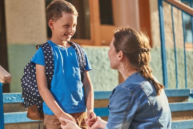 Moeder begeleidt het kind naar school