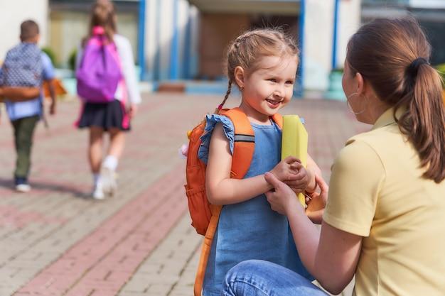 Moeder begeleidt het kind naar school.