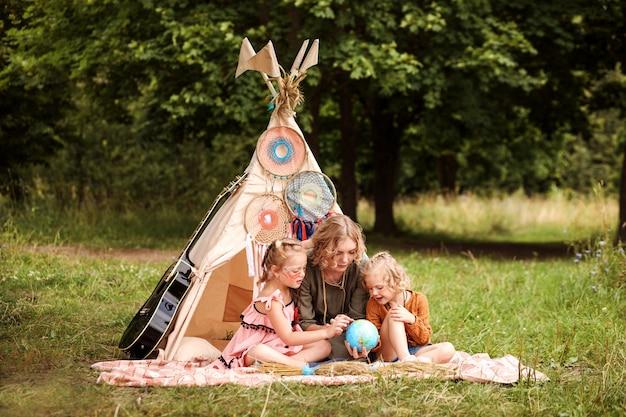 Moeder bestudeert op een speelse manier de aardrijkskunde van haar dochters. familie zit naast wigwam, tipi.
