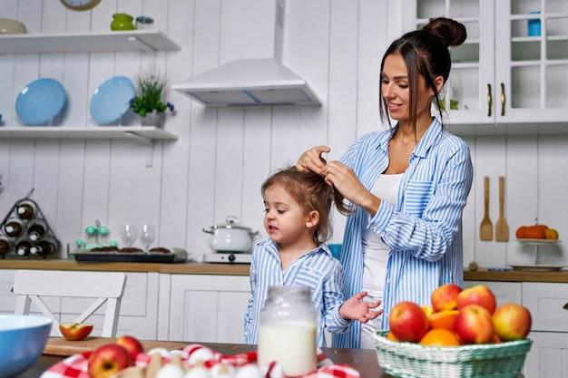 Moeder bindt haar dochter een paardenstaart en ze zullen thuis in de keuken koken.
