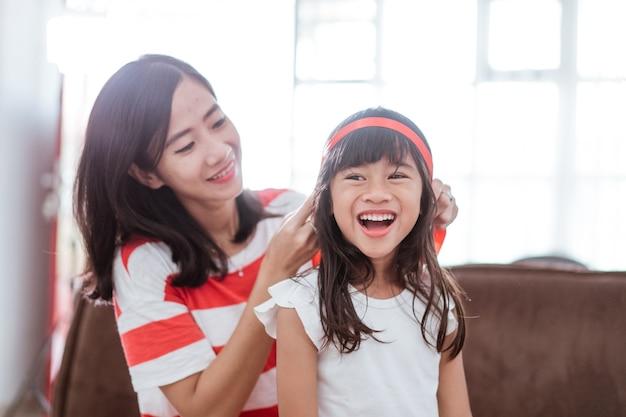 Moeder bindt rood lint op haar dochters voorhoofd