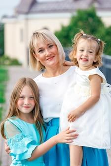 Moeder blonde met dochters in het zomerpark bij zonnig weer.