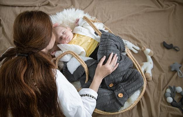Moeder boog zich over een slapende baby in een rieten wieg met een bovenaanzicht van een warme gebreide deken.