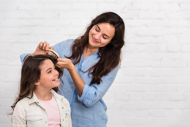 Moeder borstelt haar dochtershaar