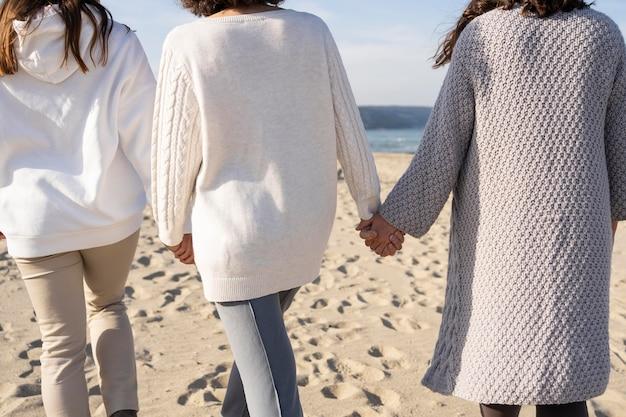 Moeder brengt tijd door met haar dochters op het strand
