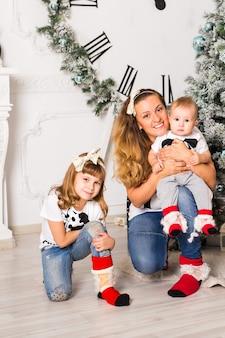 Moeder brengt tijd door met zoon en dochter in de buurt van de kerstboom.