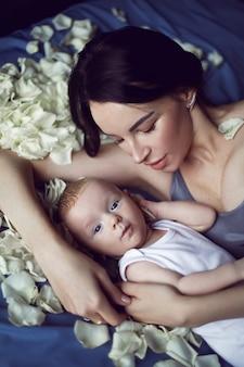 Moeder brunette met een pasgeboren jongen ligt op het bed met witte rozenblaadjes