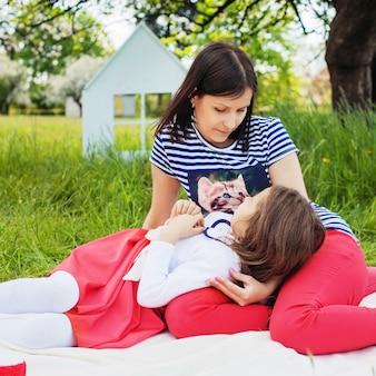 Moeder communiceert met een dochtertje in het park. plein. het concept van kindertijd, familie, vriendschap, levensstijl.
