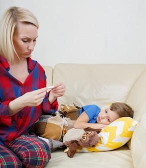 Moeder controleert de temperatuur van haar zieke zoon.