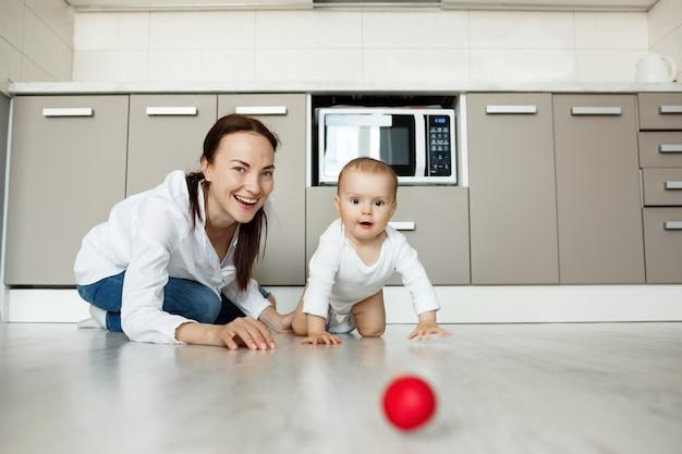 Moeder die als baby glimlacht die op vloer kruipt om bal te krijgen
