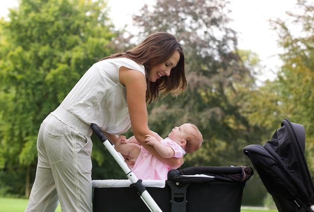 Moeder die baby in kinderwagen zet