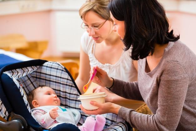 Moeder die baby voedt bij verloskundigenpraktijk