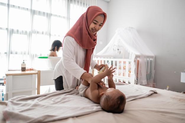 Moeder die babyolie toepast op haar baby
