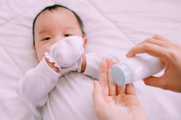 Moeder die babypoeder in haar hand voorbereidt en 2 maanden oud babyjongen op bed.