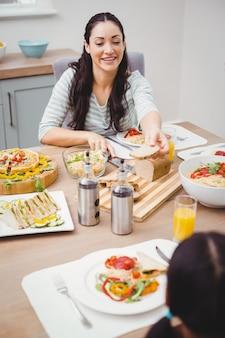 Moeder die brood geeft aan dochterzitting bij eettafel