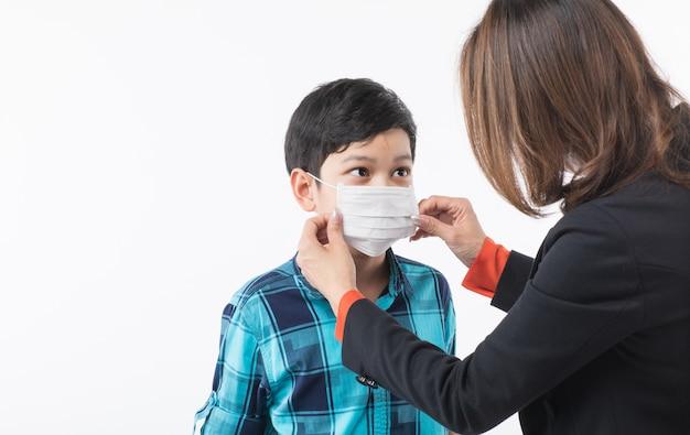 Moeder die chirurgisch masker voor zoon draagt.