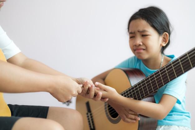 Moeder die de dochter onderwijst die leert hoe te akoestische klassieke gitaar te spelen