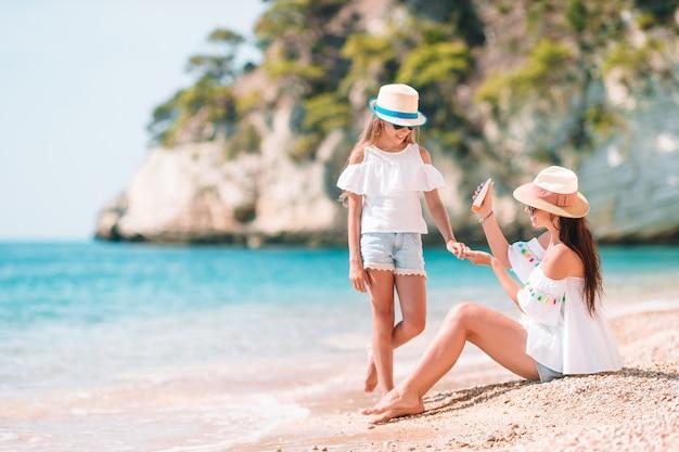 Moeder die de room van de zonbescherming toepast op haar dochter bij tropisch strand
