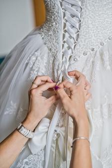 Moeder die de trouwjurk van de bruid bindt, het interieur van het hotel