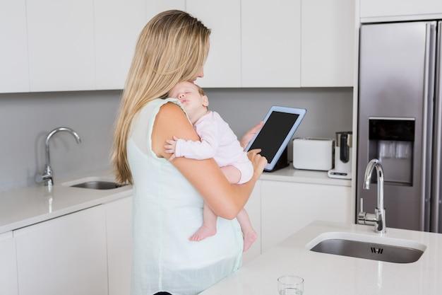 Moeder die digitale tablet gebruiken terwijl het dragen van haar baby in keuken