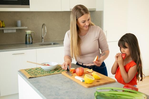 Moeder die dochter geeft om appelschijf te proeven tijdens het koken van salade. meisje en haar moeder samen koken, vers fruit en groenten snijden op snijplank in de keuken. familie koken concept
