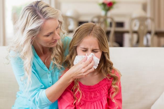 Moeder die dochter helpt die haar neus op bank blaast