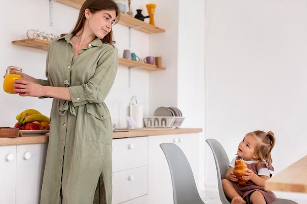 Moeder die dochter in keuken bekijkt
